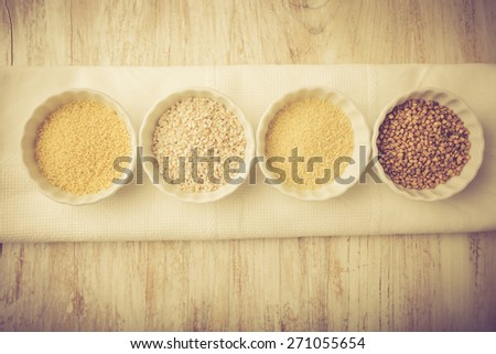 Types of grain groats on a white wood. Studio shoot with vintage mood. - stock photo