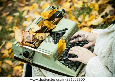 Typewriter outdoor with autumn leaves. - stock photo