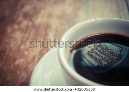 Typewriter reflection on Coffee in white cup on wood table , process in vintage style - stock photo