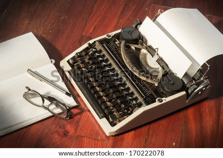 Typewriter with book and eyeglasses  - stock photo