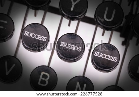 Typewriter with special buttons, success breeds success - stock photo