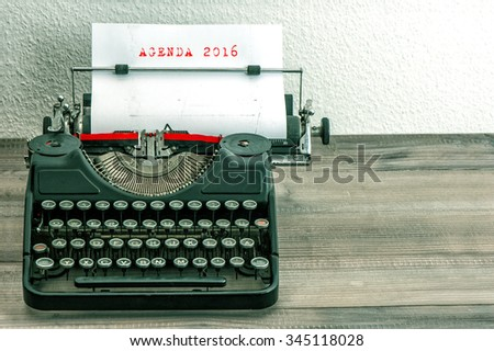 Typewriter with white paper page on wooden desk. Business concept. Sample text AGENDA 2016. vintage style picture - stock photo