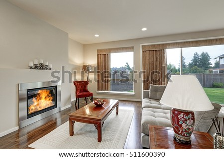 Typical American family room interior in light tones. The room has large windows, creamy tones walls, artificial fireplace and couch with grey upholstery .  Northwest, USA