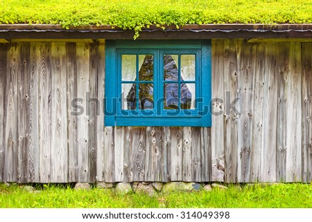 Typical ancient wooden farmhouse with blue window and grass roof in Sweden - stock photo