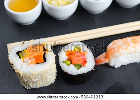 Typical asian cuisine set on black kitchen slate plate. Fish sauce in small white bowl. Chopsticks. Sushi - futomaki and nigiri.