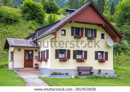 Typical Austrian architecture, beige stone house with windows with brown shutters. House with green forest background - stock photo