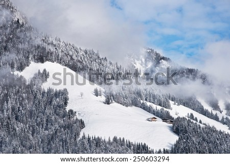 Typical austrian winter season landscape with chalets by the mountain - stock photo