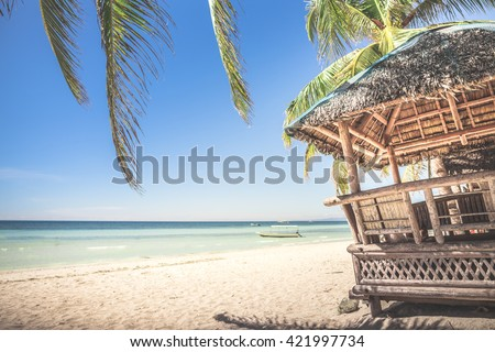 Typical bamboo hut and palm leaves standing at the white sand  beach against background with beautiful sea and cloudless blue sky on a sunny day. Panglao Island, Philippines. - stock photo