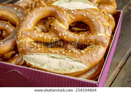 typical bavarian pretzel on old wooden table - stock photo