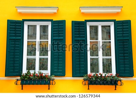 typical bavarian windows with green shutters and window box, christmas decoration - stock photo