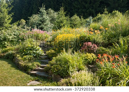 typical british garden with stone stairs and diversity of colorful flowers as hellebores, daylily, berberis and coreopsis - stock photo
