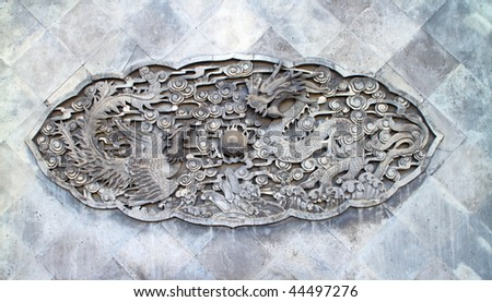 Typical Chinese carven dragon on wall - stock photo