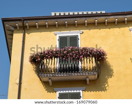Typical classical Italian house balcony with blooming flowers in Lake Garda Verona area - stock photo