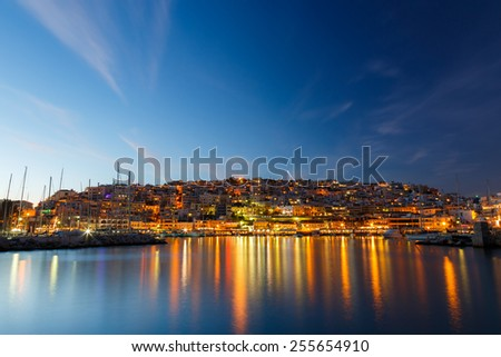 Typical colorful evening scenery in the Mikrolimano marina in Athens in the afternoon, with clouds over the city lights and many restaurants on the seafront in Greece Long exposure photography