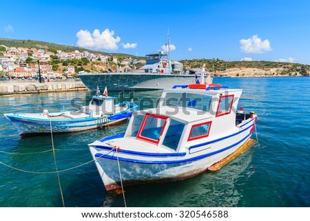 Typical colourful fishing boats with warship in background in Pythagorion port, Samos island, Greece - stock photo