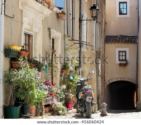 Typical courtyard with flowers and motorbike of old village in La Provence, wooden doors, windows, old street lamps, beautiful view, outdoors - stock photo