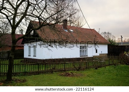 Typical czech stony cottage with small garden on highlands