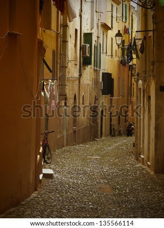 Typical dark italian alley with drying laundry and bicycles. - stock photo