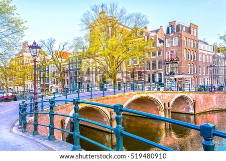 Typical Dutch dancing houses and bridges on canals in Amsterdam, Netherlands