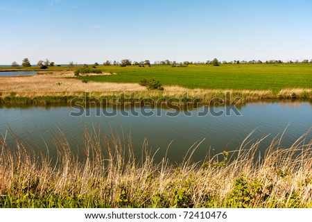 Typical Dutch flat landscape with pastures and water