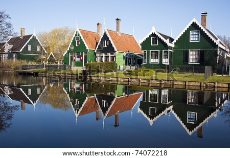 typical dutch houses reflected in water on a sunny spring day - stock photo