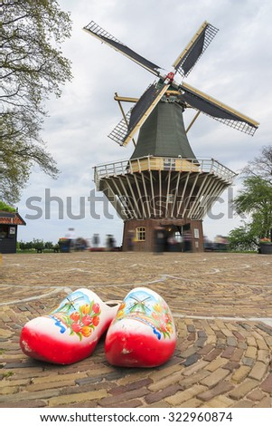 Typical dutch image of large wooden clogs (klompen) in front of a windmill  - stock photo