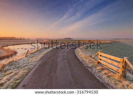Typical Dutch landscape on a frosty morning at sunrise. - stock photo
