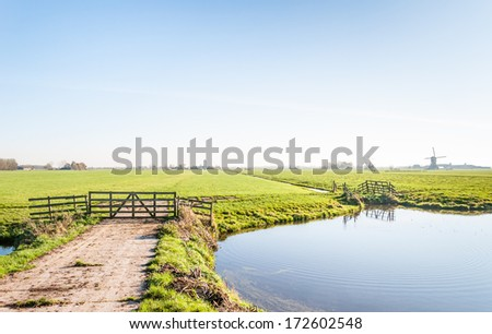 Typical Dutch landscape with a wooden fence and a natural pond in the foreground and a windmill blurred in the background. - stock photo