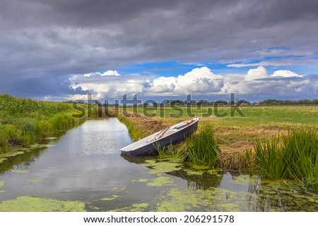 Typical Dutch Landscape with Meadows, Water and Clouds - stock photo