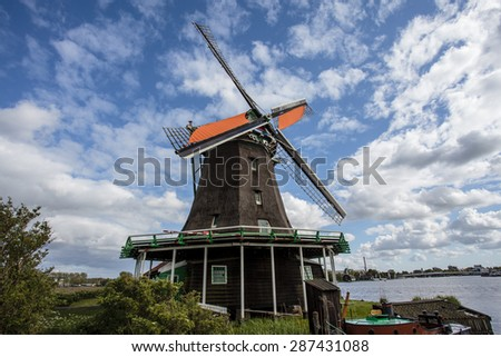 Typical Dutch landscape with windmills along a river in Zaanse Schans, Noord-Holland, The Netherlands - stock photo