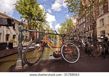 Typical dutch: Old orange bike against a medieval bridge in the citycenter from Amsterdam the Netherlands - stock photo