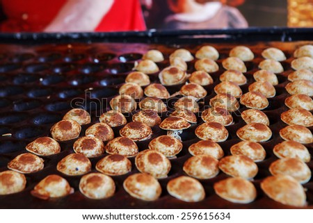 Typical Dutch poffertjes - tiny pancakes-being baked on a heavy cast iron pan - stock photo