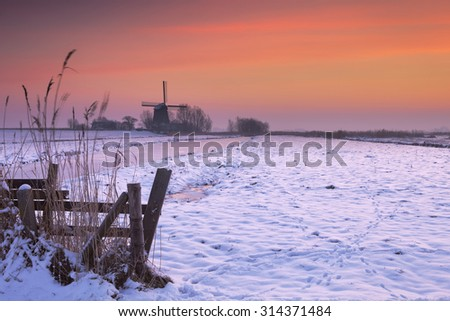 Typical Dutch polder landscape with a traditional windmill. Photographed in winter at sunrise. - stock photo
