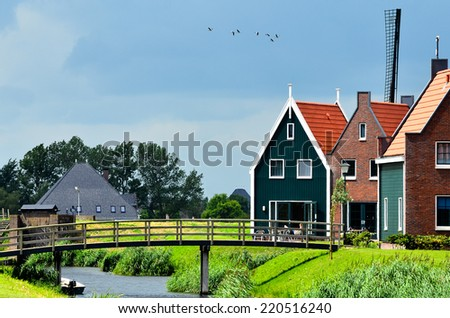 Typical Dutch Village Houses with a Mill - stock photo