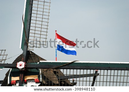 Typical Dutch windmill and national flag - stock photo