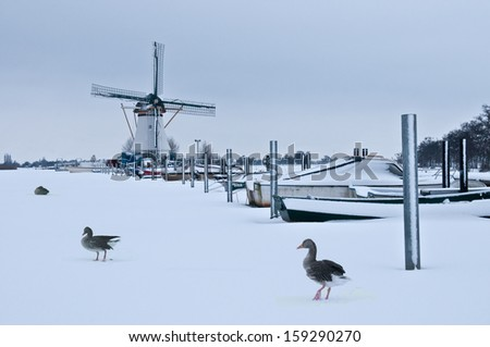 Typical dutch winter landscape with a mill and boats in twilight - stock photo