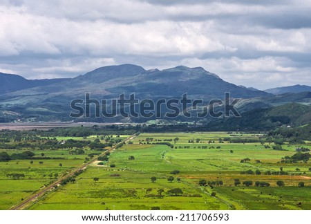 Typical example of scenery in the coastal area of west Wales. A railway line crosses flat farm land, where cattle and sheep graze in the sunshine, with the mountains of Snowdonia in the background.