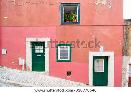Typical exterior of old houses in narrow street in Bairro Alto in Lisbon, capital of Portugal, leading to a colorful composition