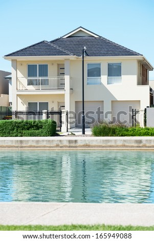 typical facade of a modern town suburban house near the pond  at noon - stock photo