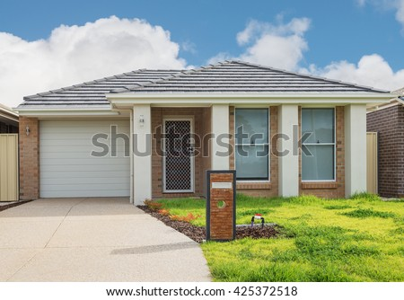 typical  facade of a new brick modern suburban  house against cloudy sky - stock photo