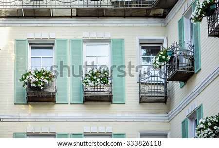 Typical facade of the old Provencal retro house with windows and wooden shutters decorated with colorful fresh flowers - stock photo