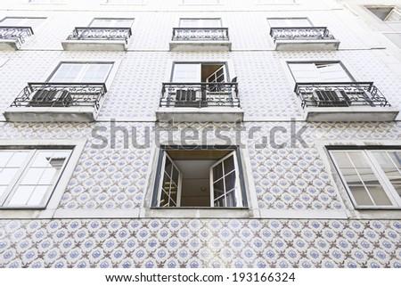 Typical facade tiles in Lisbon, facade detail of an ancient decorated - stock photo