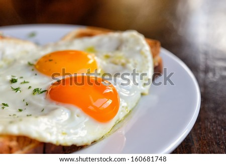 Typical french dish croque-madame with beautiful fried eggs, bread and ham, shallow DOF in natural light closeup image