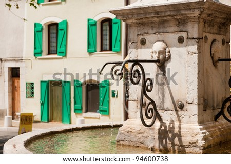 Typical French square with water fountain - stock photo