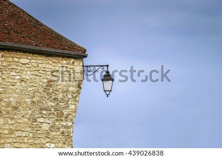 Typical french village street with retro-style lanterns, Paris region - stock photo
