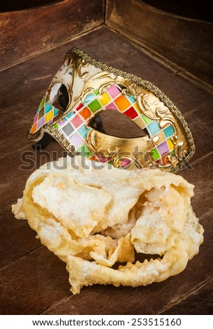 Typical fried pastry of italian carnival with venetian mask. These sweet are called in different ways, chiacchiere, Galani, cenci or frappe. - stock photo