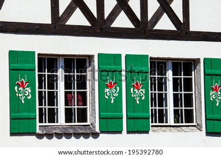 Typical germany windows with green shutters and window box - stock photo