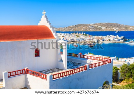 Typical Greek church overlooking Mykonos bay with port, Cyclades islands, Greece - stock photo