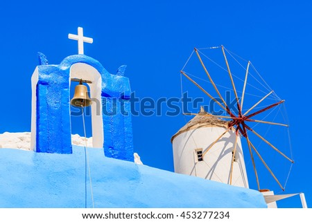 Typical Greek church tower and windmill with blue sky in background in Oia village, Santorini island, Greece - stock photo
