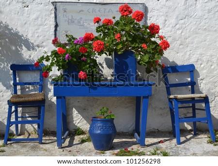 Typical greek courtyard with blue flower pots in Piskopiano on Crete, Greece. - stock photo